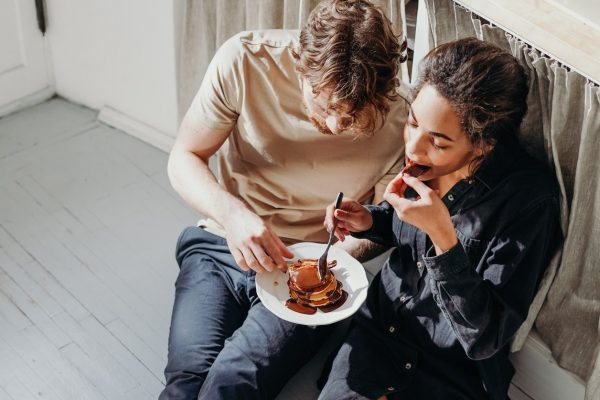 man and woman eating pancakes on white floor getting along