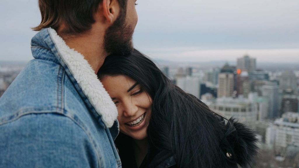 man and woman hugging city skyline