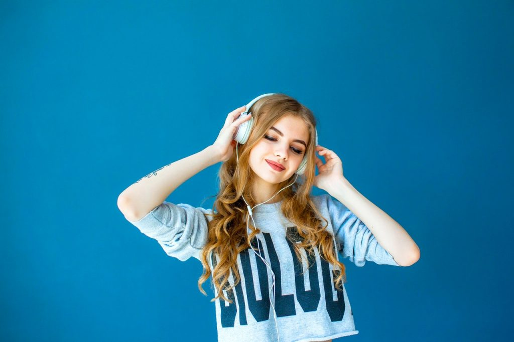 girl with headphones and blue background positive music influence