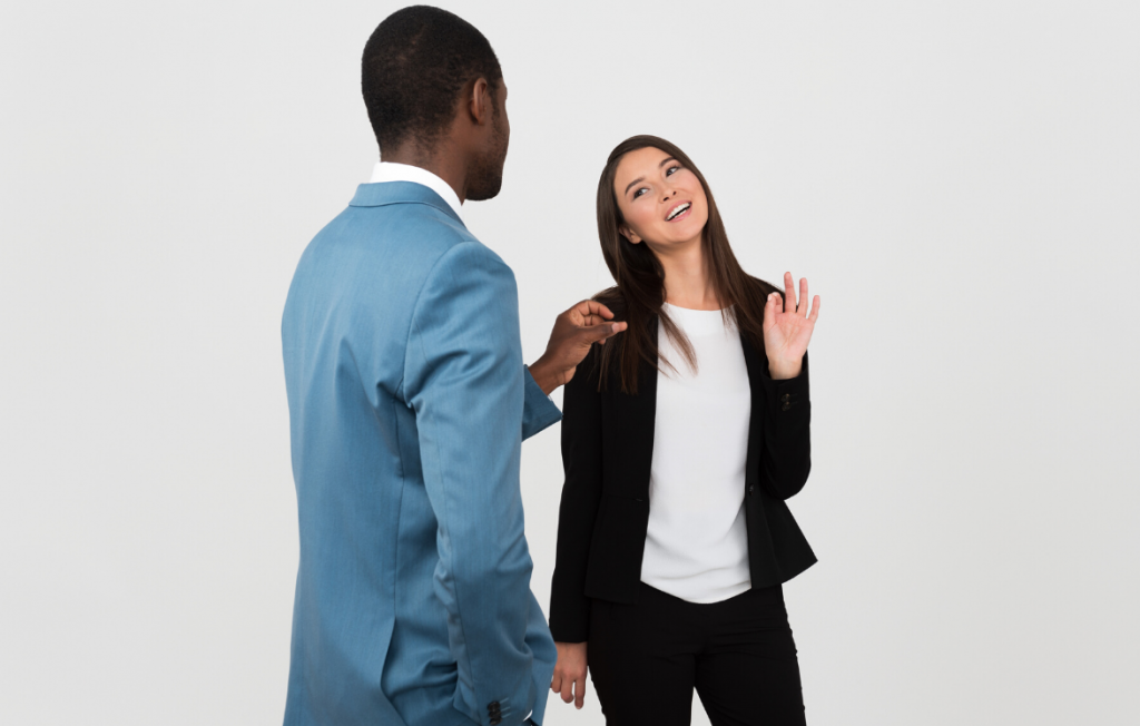 black man and white woman in suits giving compliments