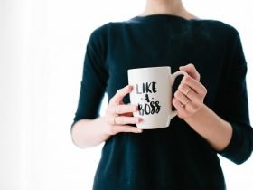woman in black shirt holding coffee cup like a boss lady