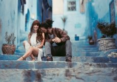 man and woman sitting on stairs surrounded by blue buildings