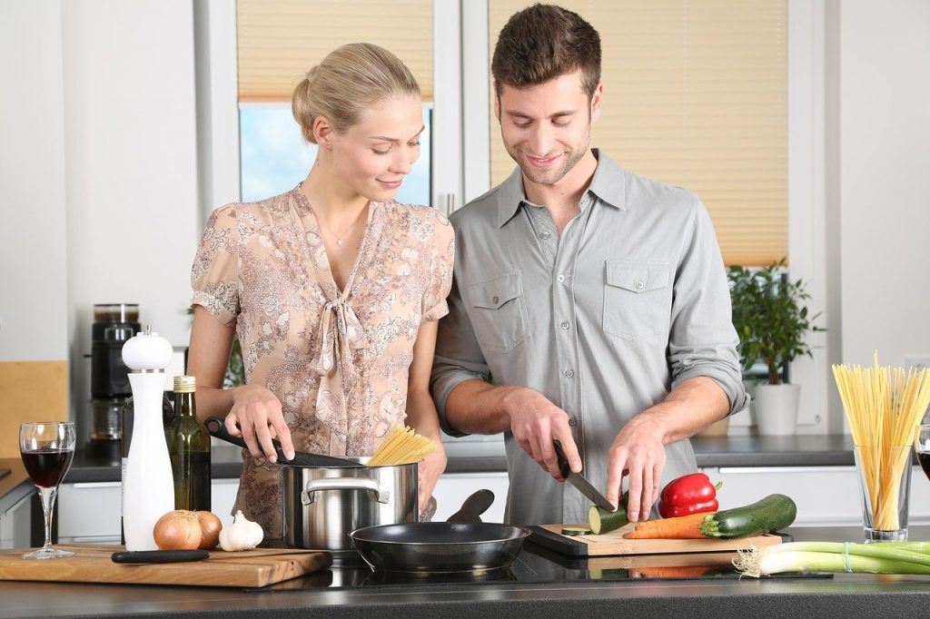 man and woman cooking in kitchen together asking relationship questions